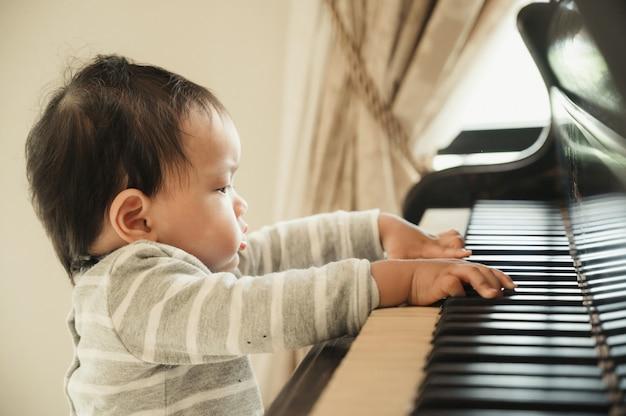 かわいい男の子は家でピアノを弾きます