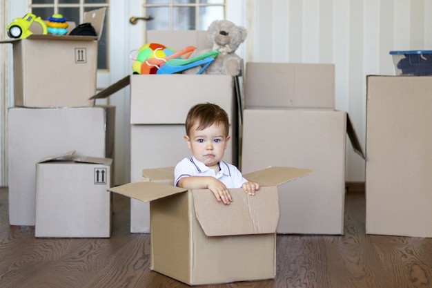 Cute little baby boy sitting inside cardboard box with big boxes full of toys on backgroun