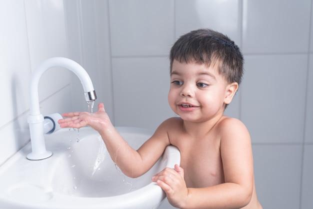 Piccolo neonato sveglio che lava la mano nel lavandino del bagno