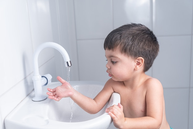 Cute little baby boy washing hand in bathroom sink
