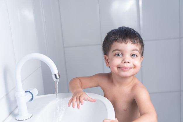 Cute little baby boy washing hand in bathroom sink