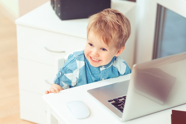 ホームオフィスでコンピューターのラップトップと携帯電話を持つかわいい男の子ガジェットと子供のコンセプト