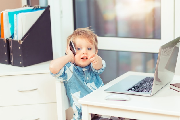 Cute little baby boy with computer laptop and mobile phone at home office smilin