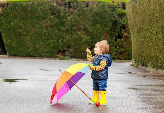 Cute little baby boy in yellow rubber boots with colorful rainbow umbrella on wet road aft