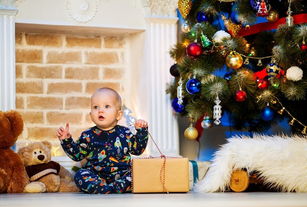 Cute little baby child boy sitting at a home interior on background of the christmas tree with gift