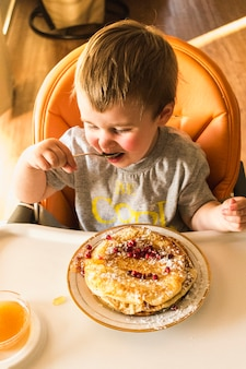 Cute little baby eating pancake on plate over the high chair