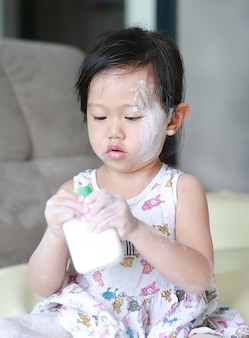 Cute little baby girl applying baby powder on her face and hand.