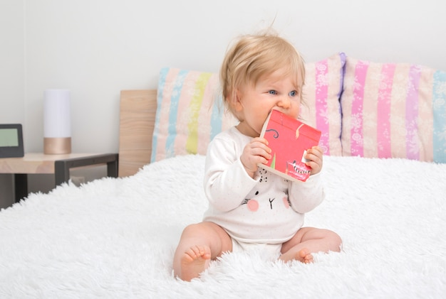Cute little baby girl in bedroom with book.