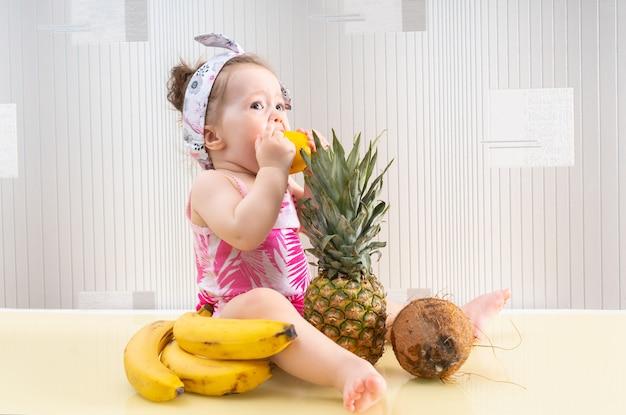 Милая маленькая девочка в розовой рубашке сидит среди тропических фруктов на поверхности стола