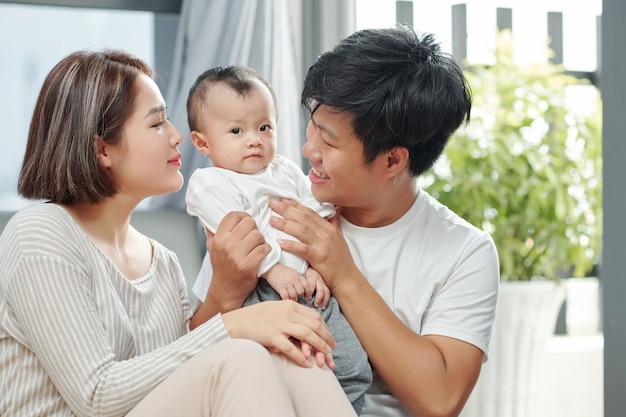 부모가 그녀를 즐겁게하려고 할 때 앞을보고 귀여운 아기 소녀