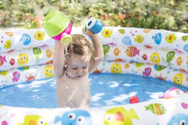 Cute little baby girl playing in a colorful inflatable pool