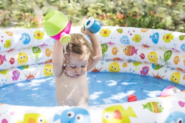 다채로운 풍선 수영장에서 노는 귀여운 아기 소녀