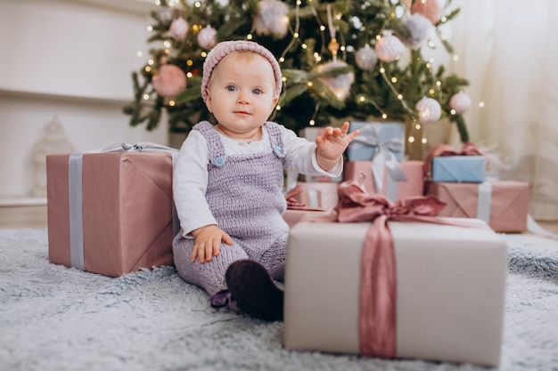 Cute little baby girl sitting by christmas presents