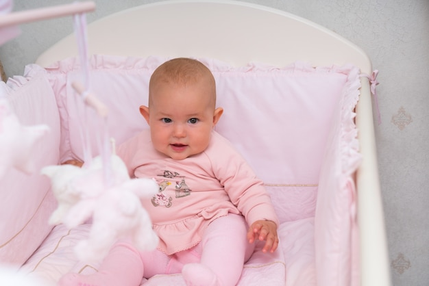 Милая маленькая девочка сидит в розовой кроватке и с любопытством смотрит в камеру крупным планом