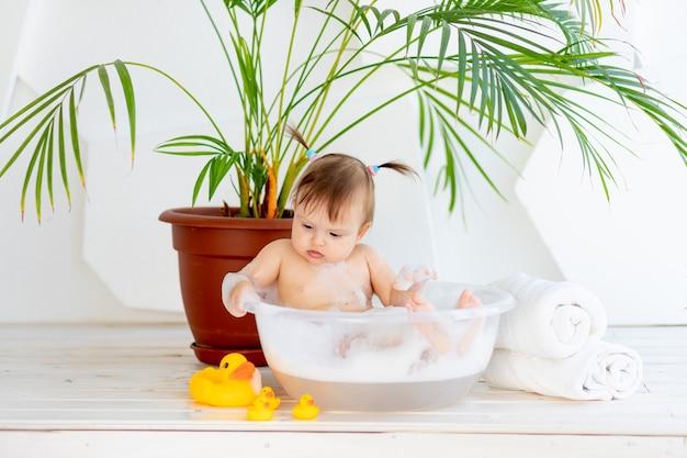 Милая маленькая девочка принимает ванну