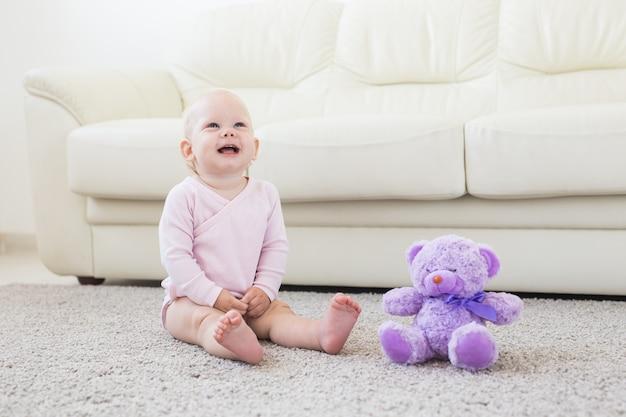カーペットの上に座っているピンクの服を着てかわいい女の赤ちゃん