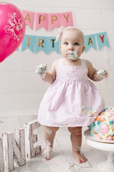 핑크 드레스를 입고 귀여운 아기 소녀 휴가 전체 샷을 축하 케이크 크림에 더러워집니다. 재미있는 여자 아이 축 하 생일 현대 축제 인테리어에서 포즈