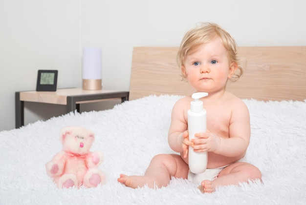 Cute little baby girl with bottle of baby oil in parent bedroom.
