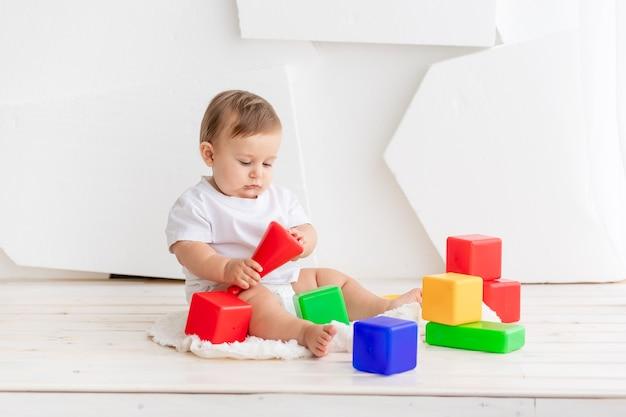 Милый маленький ребенок в белой футболке и подгузниках играет дома на коврике с яркими цветными кубиками