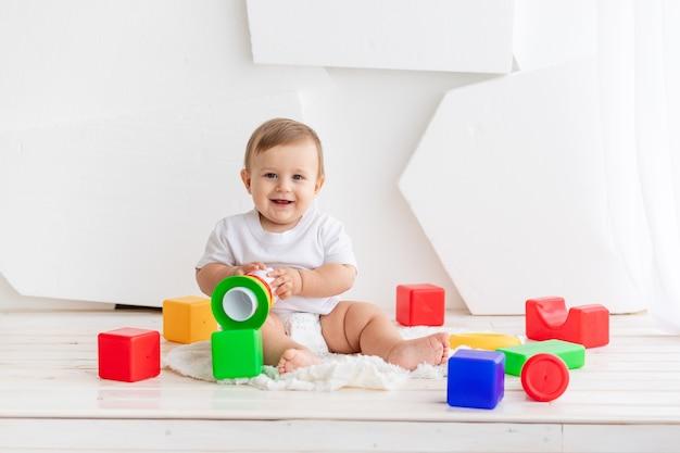 흰색 티셔츠와 기저귀에 귀여운 작은 아기가 밝은 색의 큐브와 매트에 집에서 놀고