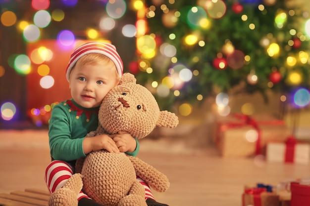 エルフの衣装を着て、クリスマスイブに家でおもちゃを持っているかわいい赤ちゃん