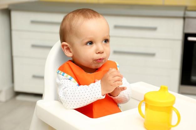 집에서 유아용 의자에 있는 귀여운 아기