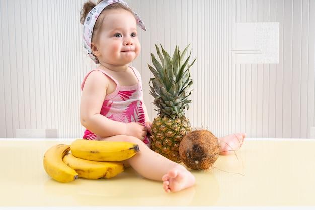 Милый маленький ребенок в розовой рубашке сидит среди тропических фруктов