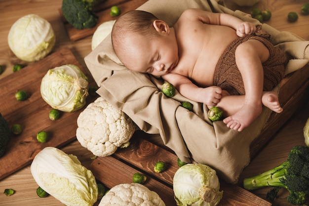Cute little baby is lying in the box with a lot of different cabbages around