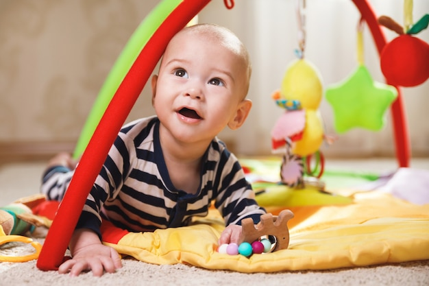 Cute little baby is playing on the activity mat