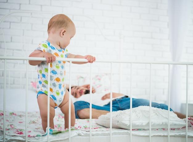 かわいい赤ちゃんがベッドの端に立っています。