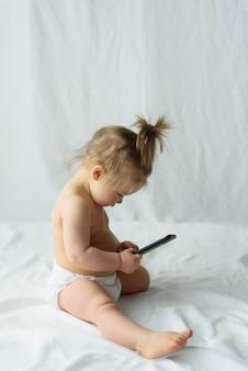 かわいい赤ちゃんは白で分離された携帯電話で話しています。