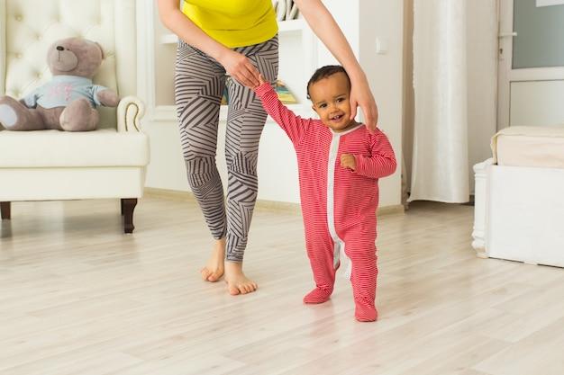 Милый маленький ребенок учится ходить, мама держит его за руки.