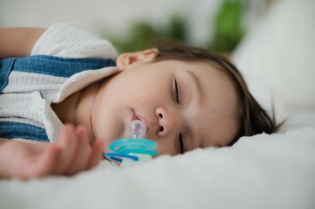 白いベッドの上で自宅で快適に休んで眠っているかわいい赤ちゃん