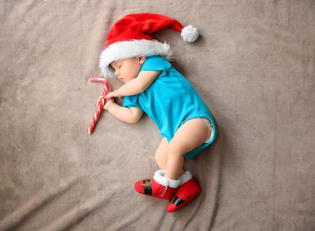 Cute little baby in santa hat sleeping on fabric