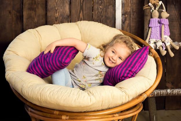 Милый маленький ребенок сидит в плетеном гнезде. украшение студии сельских пасхальных праздников.