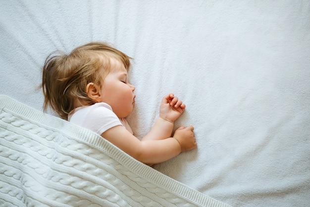 Милый маленький ребенок мирно спит на кровати у себя дома покрыты одеялом. детский дневной график сна.