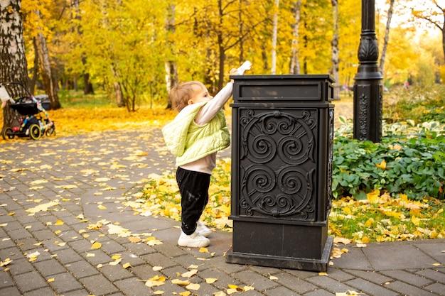 Симпатичный малыш выбрасывает мусор в мусорное ведро в осеннем парке, прививая культурные нормы с рождения