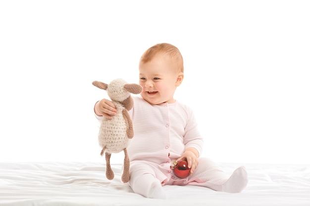 Милый маленький ребенок с мячом и игрушкой на белом полу