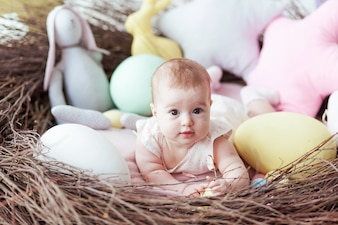 Cute little baby with colorful Easter eggs and toy rabbit lying in nest.