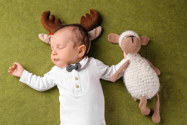 Милый маленький ребенок с оленьими рогами и игрушкой на цвете