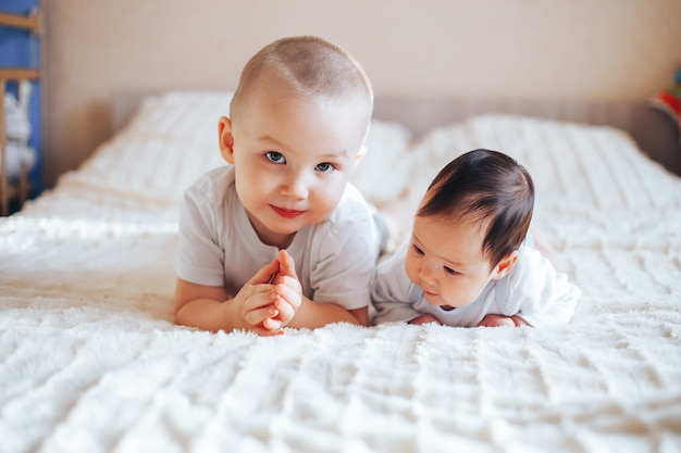 Cute little baby with elder brother lying on bed at home