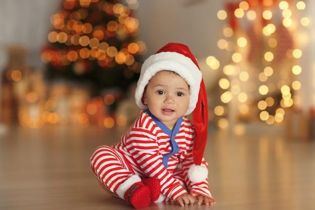 床にサンタの帽子と表面にぼやけたクリスマスライトを持つかわいい赤ちゃん