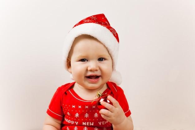 床にサンタの帽子とぼやけたクリスマスライトとかわいい赤ちゃん