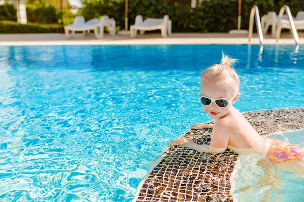 Cute little baby with sunglasses swimming in the pool.