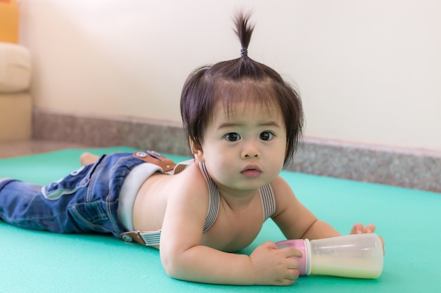 Cute little baby with tie hair enjoy playing on the floor in home