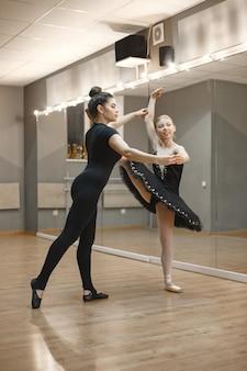 검은 발레 의상을 입은 귀여운 작은 발레리나. 젊은 아가씨가 방에서 춤을 추고 있습니다. 교사와 댄스 클래스에서 소녀입니다.