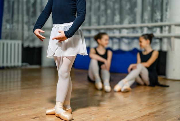 댄스 스튜디오의 귀여운 작은 발레리나가 배경에서 발레 팀과 함께 포즈를 취하고 훈련합니다. 선택적 초점입니다. 확대.