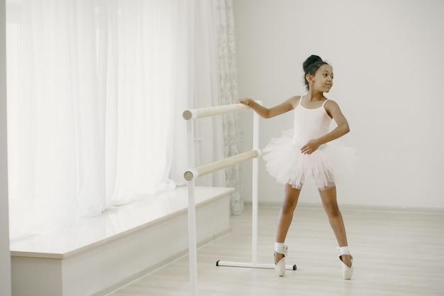 핑크 발레 의상을 입은 귀여운 작은 발레리나. pointe 신발에 아이가 방에서 춤을 추고 있습니다. 댄스 클래스에서 아이.