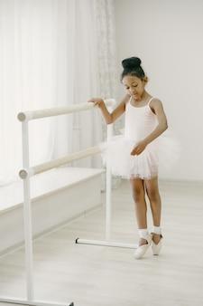 Милая маленькая балерина в розовом балетном костюме. ребенок в пуантах танцует в комнате. малыш в танцевальном классе.