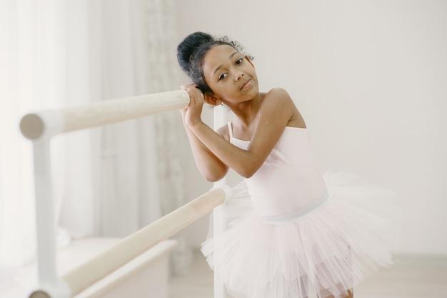 ピンクのバレエ衣装でかわいい小さなバレリーナ。トウシューズを履いた子供が部屋で踊っています。ダンスクラスの子供。
